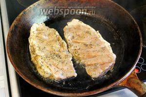 Разогреть в сковороде масло, положить мясо, убрав с него лук и чеснок, которые оставить в маринаде. Огонь печи убавить до среднего, жарить с одной стороны 5 минут.