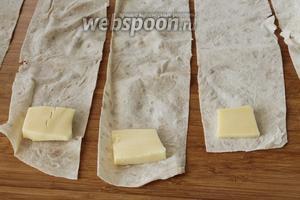 Положить на каждую полоску по кусочку сыра, нарезанного на прямоугольники средней толщины.