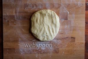 Обомните тесто и переложите на рабочую поверхность и сделайте из него плоскую лепёшку.