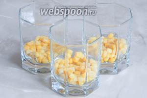 Теперь выкладываем салат слоями в прозрачные стаканы (у меня емкостью 200 мл). Вначале слой кукурузы (немного оставим для украшения).