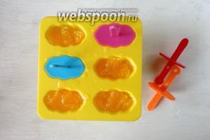 Разливаем апельсиновый сироп по формам, равномерно распределяем мякоть. Вставляем палочки и ставим в морозильную камеру на ночь.