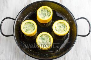Выложить в «бочонки» овощную смесь. Стараться заполнять не доверху, оставить место для яйца. Поставить форму в горячую духовку. Запекать в течение 15 минут при температуре 180°C.