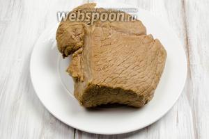 Вынуть с помощью длинной вилки кусок готового мяса. Выложить его на блюдо. Нарезать острым ножом. Подавать тёплым со свежими овощами, хреном или горчицей. При желании можно мясо охладить и подавать кусками, как холодную закуску.
