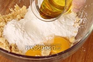Сделать в середине углубление, положить туда крахмал, пудру, ванильный сахар, яйцо и оливковое масло. Перемешать.