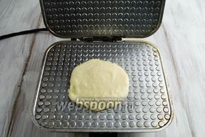 Вылить 1 столовую ложку теста на её внутреннюю поверхность. Опустить створку вафельницы, прижать её. Выпекать в течение 3,5-4 минут. Ориентируйтесь на цвет (по желанию) — светло-золотистый или ярко зажаренный.