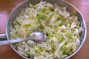 В сковороду к луку добавьте нашинкованную капусту. Тушите всё под крышкой до мягкости капусты. Капуста должна быть почти готова. Добавьте соль и перец по вкусу.