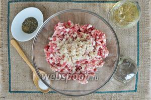 Пропустить через мясорубку чеснок. Добавить в фарш соль, перец, вермут и итальянские травы. И тщательно всё перемешать.