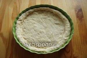 Тесто переносим и расправляем по форме блюда, делаем бортики, блюдо предварительно смазываем растительным или оливковым маслом.