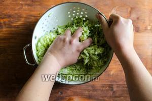 Тщательно отожмите цукини над глубокой тарелкой или миской. Лучше разделить массу на 3 части и отжимать каждую по очереди.