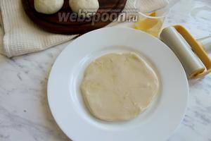 Стол смазать растительным маслом и раскатать каждый шарик теста в лепёшку, выложить на тарелку и смазать каждую растительным маслом.