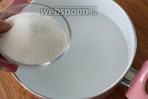 В кипящую воду положить сахар и помешать ложкой на огне до полного растворения сахара.