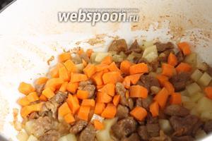 Сначала добавляем к мясу кубики картошки, перемешиваем и готовим 2 минуты, затем очередь морковки.