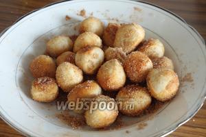 В тарелку насыпаем корицу и сахар, перемешиваем. Кладём в тарелку шарики (не все, по частям) и перемешиваем ложкой, чтобы они со всех сторон пропитались корично-сахарной обсыпкой.