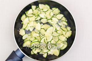 К обжаренному чесноку добавим нарезанный кабачок и на небольшом огне обжарим в течение 5-7 минут.