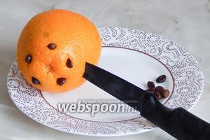 Апельсин моем под горячей водой с помощью губки. Обдаём кипятком и обсушиваем. Делаем по фрукту ровно 40 насечек ножом и в каждую втыкаем по зёрнышку кофе.