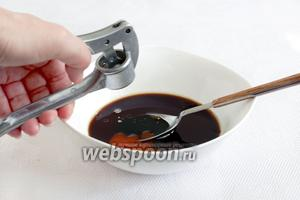 Добавить сладкий соус чили, кунжутное масло, выдавить два зубчика чеснока.