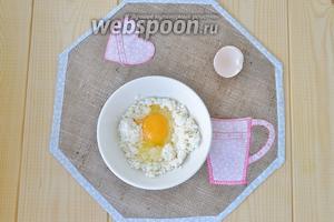 Творог растереть вилкой и добавить яйцо.