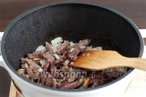 В растительном масле обжарить говядину, добавить лук и жарить еще 10 минут до лёгкого зарумянивания. Можно долить немного воды и дать мясу потушиться несколько минут до выпаривания воды.