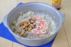 Добавить морепродукты и соевый соус, немного соли по вкусу. Перемешать и готовить пока жидкость от морепродуктов не выпарится и не впитается в рис.