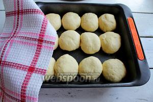 Выложить шарики в смазанную форму, накрыть полотенцем и оставить на 30 минут в тёплом месте, чтобы они ещё подошли.