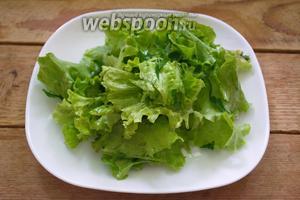 На блюдо выкладываем салатные листья.