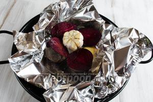 В первую очередь нужно запечь свёклу, чеснок и корень имбиря. Свёклу вымыть, разрезать пополам. У головки чеснока срезать корешок. Взбрызнуть овощи оливковым маслом. Завернуть в фольгу. Поставить для запекания в горячую духовку. Запекать в течение 1-1,5 часов до мягкости при температуре 200 °C.