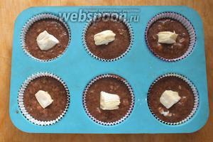 Разложите тесто по формочкам для маффинов, в середину каждого маффина вдавите по кусочку сыра бри.