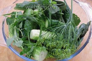 Огурчики хорошо промыть в проточной воде, отрезать попки и переложить травами в посуде, в которой будете их солить.
