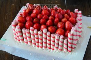 Украшаем готовый торт вафельными трубочками со вкусом клубники.