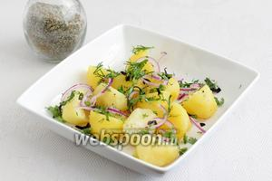 Отваренный картофель очистить и разрезать пополам. Выложить на дно салатника, посыпать половиной лука и всей зелени, посолить морской солью с травами.