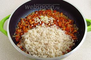 Всыпать рис и положить чеснок.