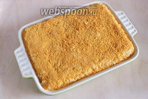 На лук положить вторую половину риса. Полейте оставшимся растопленным маслом и хорошенько присыпьте сухарями.