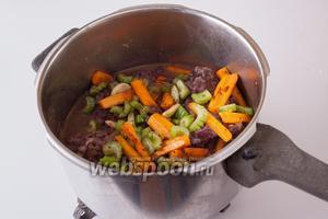 Пересыпаем обжаренные овощи в кастрюлю к мясу и вину и тушим их на слабом огне 50 минут.