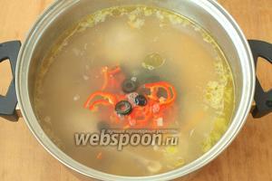 Добавить в суп нарезанные оливки и сладкий перец.