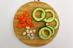 Подготовим все ингредиенты. Овощи промываем и обсушиваем. Кабачки разрезаем на кружки шириной, примерно 0,5 см. Серединку извлекаем обычной формой или рюмочкой. Чеснок очищаем от шелухи. Морковку нарезаем кружочками.