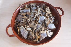 В огнеупорную форму для выпечки, смазанную маслом, выложите кусочки хека и грибы поджаренные с луком.