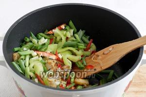 Через несколько минут в сотейник добавить зелёный лук, измельченный чеснок и перцы. Жарить помешивая одну минуту.