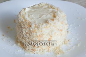 Обсыпаем бока пирожных бисквитной крошкой. Плотно прижимаем ладонями, чтобы крошка хорошо приклеилась. Крем очень нежный, поэтому пока с пирожными нужно работать аккуратно, чтобы слои не съехали. Потом крем в холодильнике схватится и станет более плотным.
