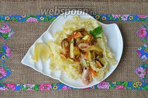 Выкладываем на тарелку пасту, а затем соус из овощей с морепродуктами, украсить лимоном и зеленью.