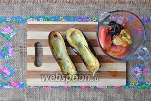 Из баклажанов ложкой удалить немного мякоти, чтобы поместились сосиски. Мякоть от баклажанов, зубки чеснока и базилик, а также помидор, разрезанный на 4 части, поместить в чашу для взбивания.