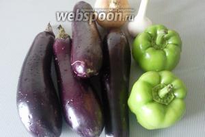Подготовим продукты. Баклажаны и перцы вымоем и проткнём вилкой в нескольких местах. Лук, зелень и чеснок помоем.