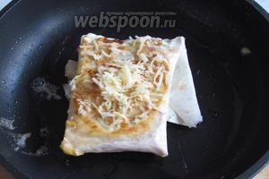 Положить на разогретую сковороду с растительным маслом, обжарить с двух сторон на среднем огне, даже чуть меньше, нужно чтобы яйцо приготовилось и не было сырым, а лаваш не подгорел. Перевернув на другую обжаренную сторону, посыпать тёртым сыром.