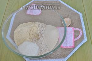 В миску выложить измельчённые хлопья, миндальную муку, кокосовую стружку, коричневый сахар  и соль. Перемешать.