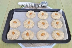 Прижать печенье ладонью и вдавить миндаль. Поставить в разогретую духовку и выпекать при 170ºC 25 минут. Если печенья маленькие, то время выпечки меньше.