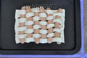 Половинки сосисок аккуратно заправить в разрезы начиная от правого края по одной. Получившейся плетёнке дать полежать минут 15 и выпекать в духовке при 170ºC пока не зарумянится 15 - 20 минут.