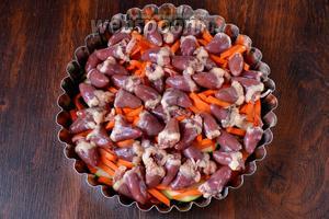 Далее раскладываем равномерно морковь, куриные сердечки, солим и перчим по вкусу.
