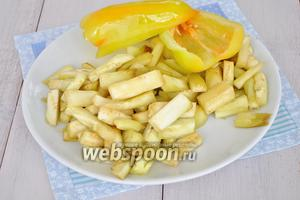 Баклажаны очистить от кожи и нарезать соломкой среднего размера. Из перца удалить семена и разрезать его вдоль на 2 части. Сбрызнуть маслом.