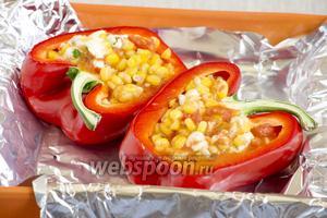 Моцареллу мелко нарезать или нартереть. Добавить в кукурузную массу. Полученной начинкой наполнить «лодочки» из перца. Накрыть сверху фольгой.