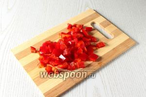 Перец очистите от семян, нарежьте кубиками или соломкой.