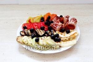 Выложить на блюдо овощи, бекон, сыр и маслины. Полить заправкой и подавать с поджаренным хлебом.